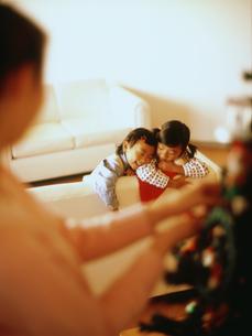 クリスマスツリーを飾る母親とソファにもたれかかる子供2人の写真素材 [FYI02067391]