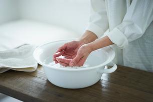 ウォッシュタブの水をすくう女性の手元の写真素材 [FYI02067416]