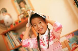 ノートを頭に置く女の子の写真素材 [FYI02067435]