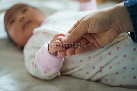 赤ちゃんの手に触れる父親の手元の写真素材 [FYI02067461]