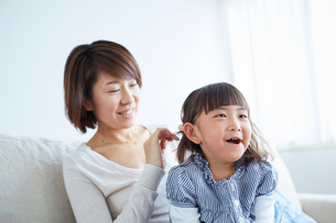 女の子の髪を結う母親の写真素材 [FYI02067471]
