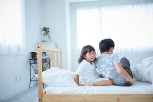 ベッドに座る兄妹の写真素材 [FYI02067506]