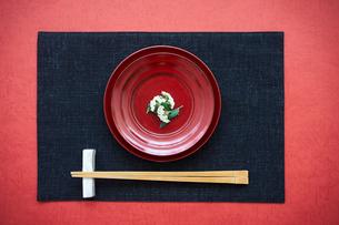花をのせた赤い皿と箸の写真素材 [FYI02067518]