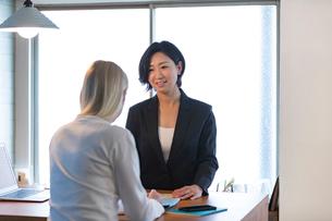 外国人女性と話す旅行代理店の日本人スタッフの写真素材 [FYI02067531]