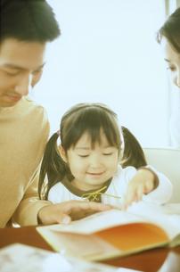 絵本を見る女の子と両親の写真素材 [FYI02067540]