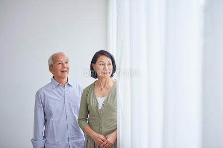 窓辺に立つシニア夫婦の写真素材 [FYI02067586]