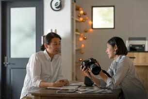 カメラを持ちミーティングをする日本人男女の写真素材 [FYI02067611]