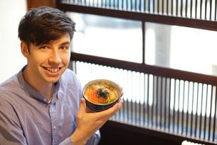 うにいくら丼を持つ外国人男性の写真素材 [FYI02067627]