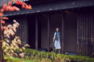 キャリーバッグを持ち廊下を歩くミドル女性の写真素材 [FYI02067677]