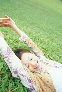 草原に寝転ぶ女性の写真素材 [FYI02067764]