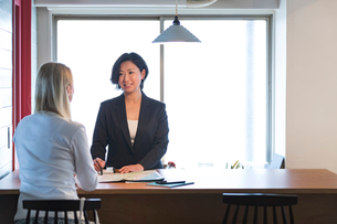 外国人女性と話す旅行代理店の日本人スタッフの写真素材 [FYI02067914]