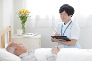 ベッドに横たわるシニア男性と笑顔の男性介護士の写真素材 [FYI02067973]