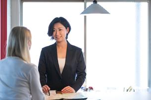 外国人女性と話す旅行代理店の日本人スタッフの写真素材 [FYI02067974]