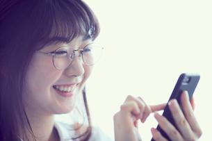 スマートフォンを操作するメガネをかけた女性の写真素材 [FYI02068086]