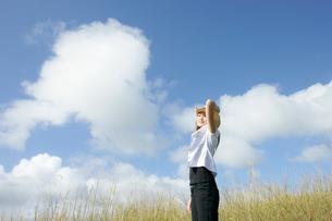 青空と草原に立つ女性の写真素材 [FYI02068142]