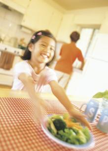 ダイニングテーブルに料理を運ぶ女の子の写真素材 [FYI02068158]