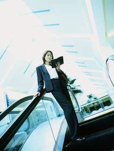 エスカレーターに乗るビジネスウーマンの写真素材 [FYI02068213]