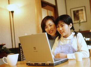 パソコンに向かう母親と女の子の写真素材 [FYI02068216]