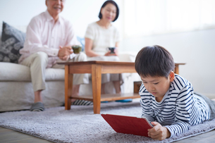 タブレットPCを見る男の子とソファに座るシニア夫婦の写真素材 [FYI02068306]