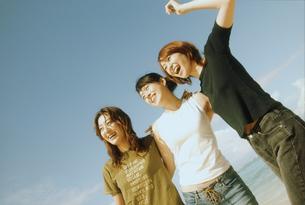 浜辺で肩を組む女性3人の写真素材 [FYI02068311]