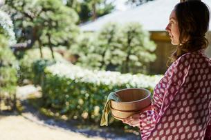 風呂桶を持ち庭を眺める浴衣姿の外国人女性の写真素材 [FYI02068356]