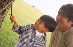 草原の父親と男の子の写真素材 [FYI02068393]