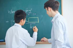 板書する男子中学生と外国人講師の写真素材 [FYI02068407]