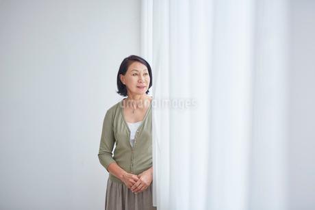 窓辺に立つシニア女性の写真素材 [FYI02068454]