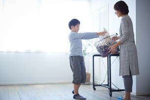 洗濯かごを持つ母親と手伝う男の子の写真素材 [FYI02068529]