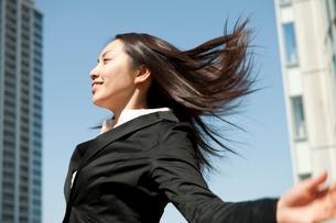 オフィス街で髪の毛をなびかせて風を受けるスーツ姿の女性の写真素材 [FYI02068576]