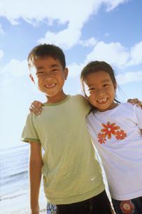 浜辺で肩を組む男の子と女の子の写真素材 [FYI02068591]