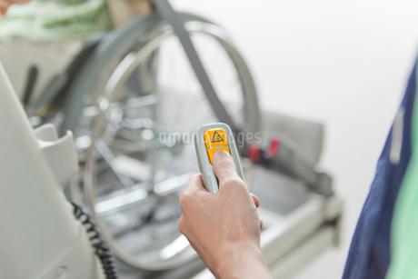 介護車両のリフトを操作する介護士の手元の写真素材 [FYI02068649]