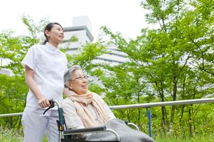 公園を散歩する車いすに乗ったシニア女性と女性介護士の写真素材 [FYI02068654]