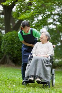 車いすに乗ったシニア女性と話す女性介護士の写真素材 [FYI02068679]