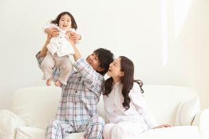 ソファで赤ちゃんを抱き上げる父親と笑顔で見守る母親の写真素材 [FYI02068691]