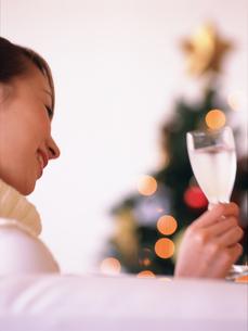 グラスを持つ女性とクリスマスツリーの写真素材 [FYI02068734]