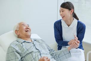 ベッドで横になるシニア男性と笑顔で話す看護師の写真素材 [FYI02068743]