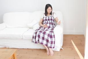 スマートフォンでメールをチェックする妊婦の写真素材 [FYI02068764]