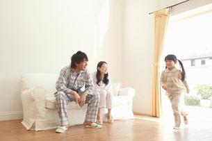 リビングを走り回る娘を笑顔で見守る父母の写真素材 [FYI02068766]