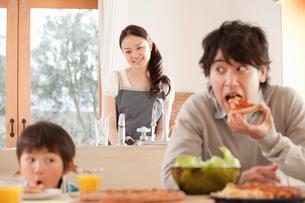 食卓でピザを頬張る父子と笑顔で見守る母親の写真素材 [FYI02068773]