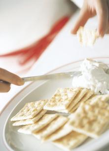 クラッカーにクリームチーズを塗るの写真素材 [FYI02068775]