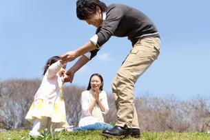赤ちゃんの手を引き歩かせる父親と見守る母親の写真素材 [FYI02068782]
