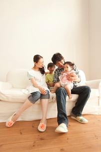 ソファで赤ちゃんを抱く父親を見守る母と息子の写真素材 [FYI02068787]