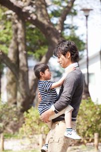 公園で子供を抱く父親の写真素材 [FYI02068794]