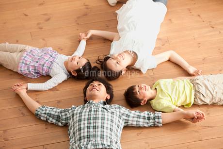 手をつないで寝そべる若い両親と子供達の写真素材 [FYI02068798]