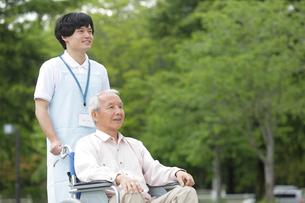 車椅子に乗るシニア男性と男性介護士の写真素材 [FYI02068812]