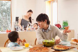 食卓でピザを頬張る父子と笑顔で見守る母親と娘の写真素材 [FYI02068814]