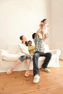 赤ちゃんを抱き上げる父親と笑顔で見守る母親と息子の写真素材 [FYI02068826]