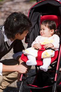 ベビーカーに乗った赤ちゃんに話しかける若い父親の写真素材 [FYI02068833]