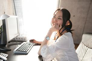 オフィスでデスクに座りPCを使う笑顔の女性の写真素材 [FYI02068856]